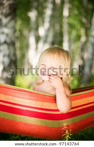 Adorable baby sit in hammock under trees - stock photo