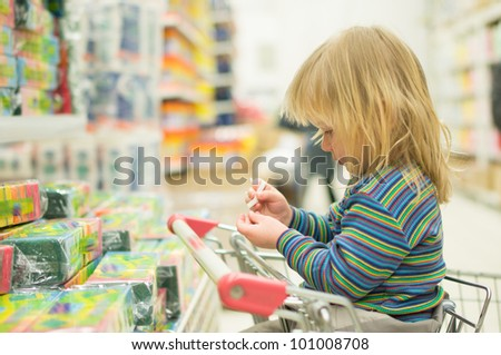 Adorable baby sit on cart in supermarket - stock photo