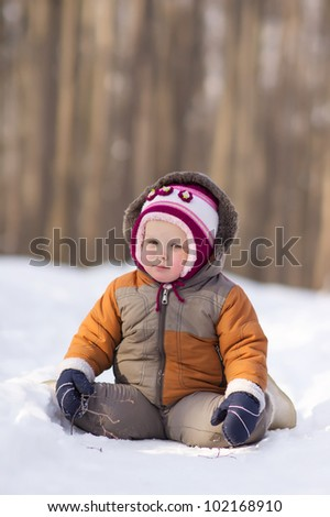 Adorable baby sit on snow road in park