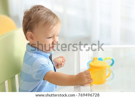 Adorable baby sitting at table with drinking bottle indoors
