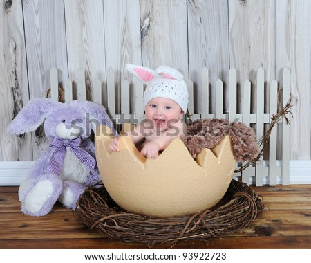 adorable baby sitting in giant easter egg with hat and bunny - stock photo