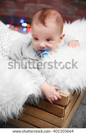 Adorable baby sitting in wooden box with fluffy plaid against brick wall background