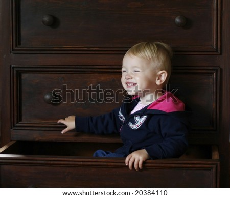 adorable baby sitting inside bureau drawer - stock photo