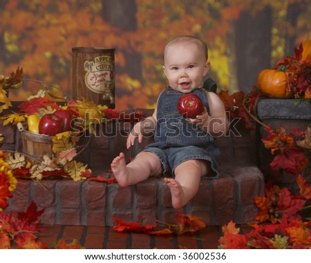 Adorable baby sitting on a brick stair holding an apple in this fall/Halloween scene - stock photo