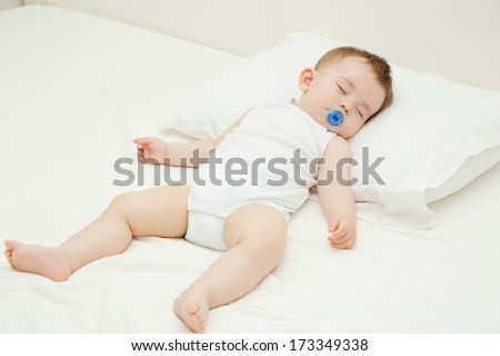 Adorable baby sleeping in the parents bed with pacifier, full body portrait,  indoors shot, copy space. - stock photo