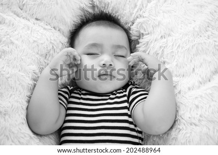 Adorable baby sleeping on a blanket. Black and white  - stock photo