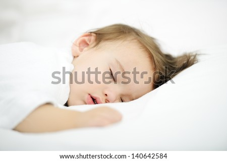 Adorable baby sleeping on white bed with copy space - stock photo