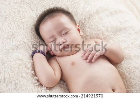 adorable baby sleeping on white blanket - stock photo