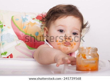 Adorable baby trying to reach favorite food - stock photo