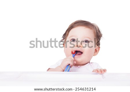 Adorable baby using toothbrush for the first time - stock photo