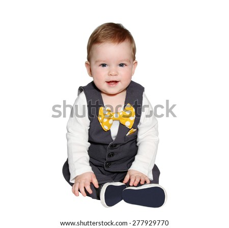 adorable baby wearing classic vest and colorful bowtie looking at camera on white background