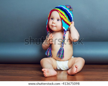 adorable baby wearing diapers and a warm winter hat - stock photo