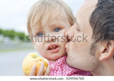 Adorable baby with big blue eyes eating an apple. Father and his little daughter outdoors. Daddy kisses small lovely child. Happy moments in childhood. Close family relationships. Colorful photo - stock photo