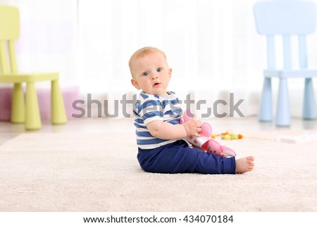 Adorable baby with pink bear on a floor - stock photo