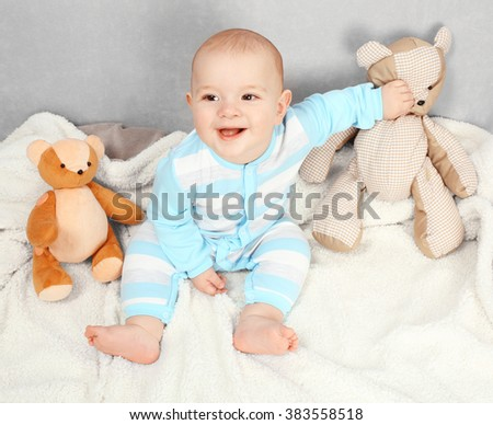 Adorable baby with teddy bears on sofa in the room, close up - stock photo
