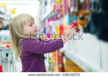 Adorable baby with toys on shelves in mall - stock photo