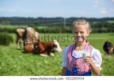 Adorable  Bavarian girl drink milk on the meadow with cow  in Germany - stock photo