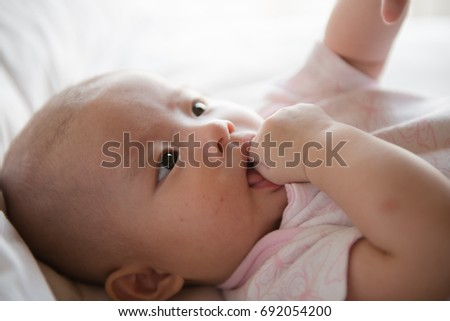 Adorable beautiful baby girl lying on the bed