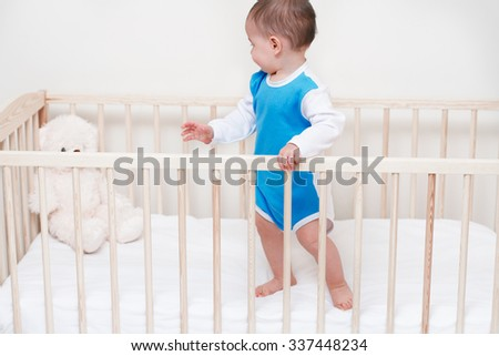 Adorable beautiful baby toddler look at bear in the bed on white background