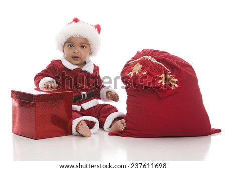 Adorable biracial baby dressed as Santa Clause and sitting next to a Christmas present and sack.  Isolated on white. - stock photo