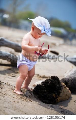 Adorable biracial baby on the beach. - stock photo