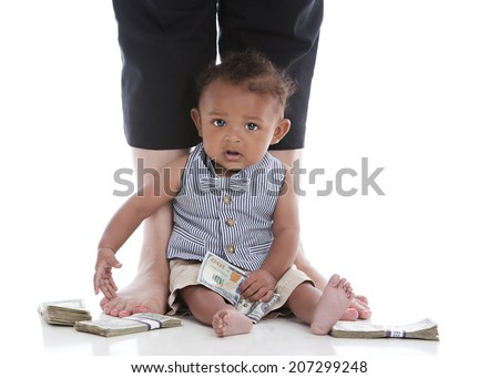 Adorable biracial baby sitting propped against his mother's legs, holding a hundred dollar bill with piles of money around him.  Isolated on white. - stock photo