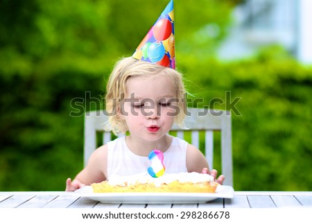 Adorable birthday girl making wish blowing candles on the cake. 3 years old toddler kid celebrating and enjoying part outdoors on summer day. - stock photo