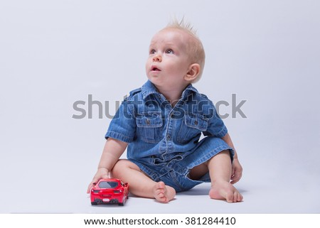 Adorable blond baby sitting and playing with a toy car. Little fashionable kid in denim suit. Adorable child sitting on the floor isolated on white background. - stock photo