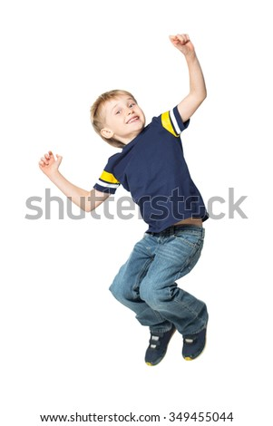 Adorable blond boy jumping and raises his hands up. Isolated on white background. Shooting in the studio - stock photo