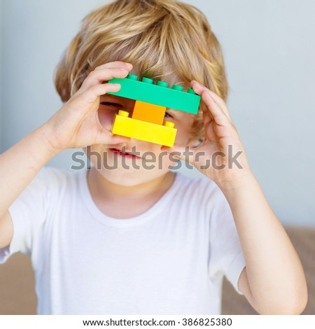 Adorable blond child playing with lots of colorful plastic blocks indoor. Active kid boy having fun with building and creating. - stock photo