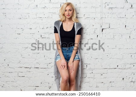 Adorable blond girl against the wall with charming smile and summer outfit. - stock photo