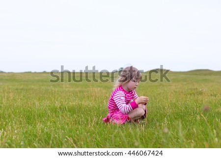 adorable blond girl in preschool age wearing bright pink clothing playing outdoors in green grass on rural field on cloudy summer day  - stock photo
