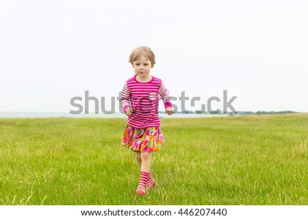 adorable blond girl in preschool age wearing bright pink clothing running outdoors in green grass on rural field on cloudy summer day  - stock photo