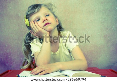 adorable blond girl preschooler over open book - stock photo