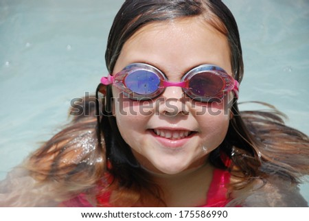 Adorable blond girl smiling in the pool wearing goggles
