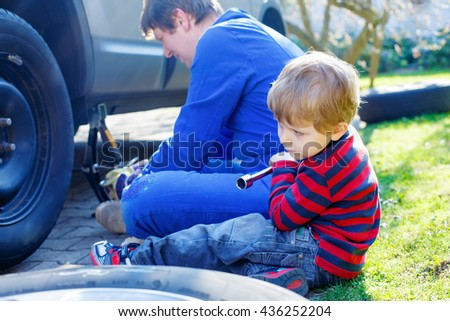 Adorable blond kid boy and his father changing wheels on car with pneumatic wrench. Man in uniform teaching his son working with tools. - stock photo