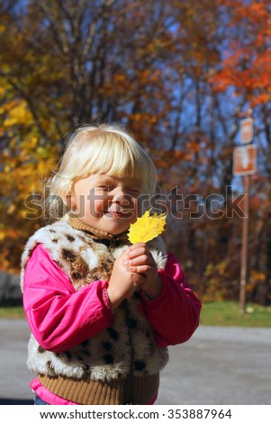 Adorable blond little girl with an autumn yellow leaf  - stock photo