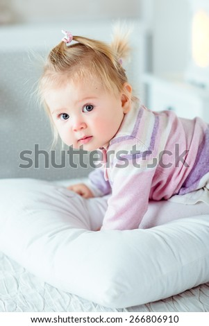 Adorable blond little girl with big grey eyes and plump cheeks staying on hands and knees on white bed in bedroom. White interior, bed, pillow, night lamp