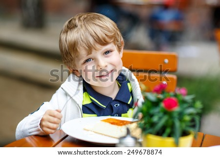 Adorable blond little kid boy, laughing and eating cake in an outside cafe in summer in an old city center in Germany on warm summer day. - stock photo