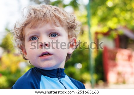 Adorable blond toddler boy in summer garden on sunny day, outdoors. - stock photo