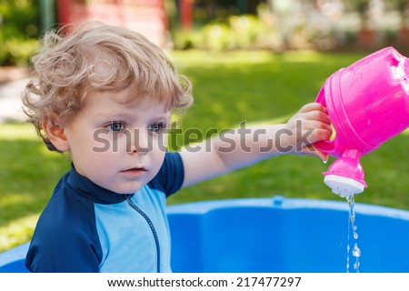 Adorable blond toddler boy playing with water in summer garden on sunny day, outdoors.