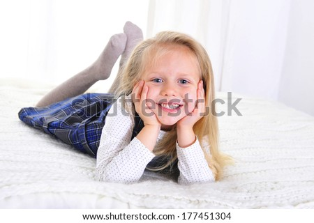 Adorable blonde blue eyed little girl lying happy on bed isolated on white background - stock photo