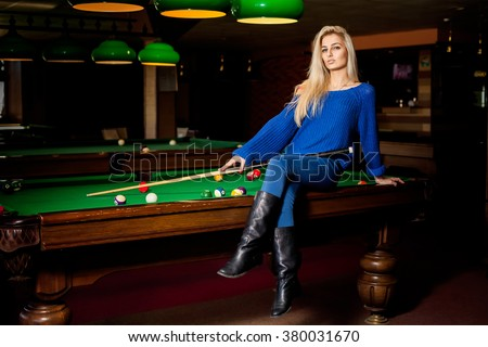 Adorable blonde fashion woman posing on pool table with the cue. Billiard sport concept. Pool billiard game. American pool billiard. - stock photo