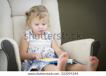 Adorable Blonde Haired Blue Eyed Little Girl Reading Her Book in the Chair. - stock photo