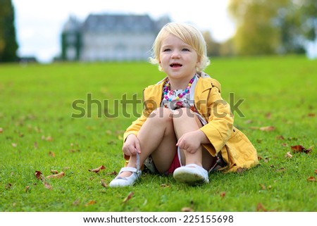 Adorable blonde little child, a toddler girl wearing yellow jacket and colorful necklace, sitting on green lawn in the park in front of the castle - stock photo