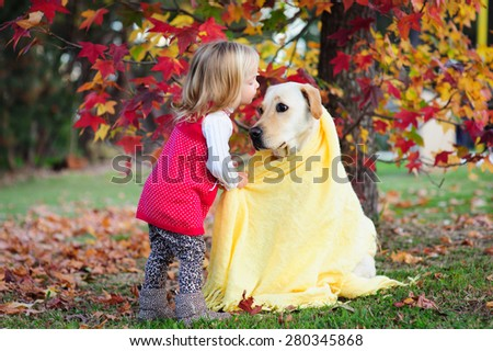 Adorable blonde little girl kissing her dog, a yellow labrador wrapped in a cozy warm blanket in a park with autumn leaves in the background - stock photo