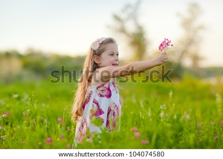 Adorable blonde little girl on the meadow with flowers - stock photo