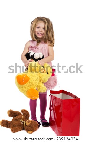 Adorable blonde little girl with pink dress holding her favorite plush toys over white background - stock photo