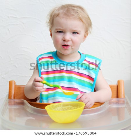 Adorable blonde toddler girl wearing colorful bib eating porridge with spoon sitting indoors in high chair with table against a white wall - stock photo