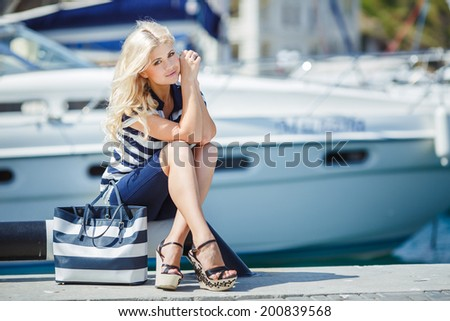 Adorable blonde woman wearing sea shorts and sexy sailor T-shirt sitting on yachts background and the sea - stock photo